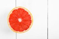 Rebanada roja fresca del pomelo en la tabla Imagen de archivo libre de regalías