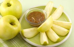 Rebanadas amarillas de Apple con la inmersión del caramelo Fotos de archivo