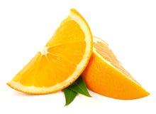 Rebanadas anaranjadas de la fruta con las hojas Imagen de archivo libre de regalías