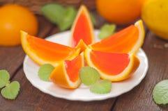 Rebanadas anaranjadas de la jalea en una placa Fotografía de archivo libre de regalías