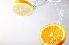 Rebanadas anaranjadas en agua Fotografía de archivo libre de regalías