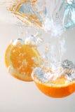 Rebanadas anaranjadas en agua Imágenes de archivo libres de regalías