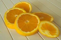 Rebanadas anaranjadas en la tabla de madera imágenes de archivo libres de regalías