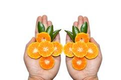 Rebanadas anaranjadas en las manos en el fondo blanco Foto de archivo