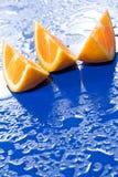 Rebanadas anaranjadas en superficie azul Fotos de archivo libres de regalías