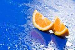Rebanadas anaranjadas en superficie azul mojada Imagenes de archivo