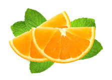 Rebanadas anaranjadas frescas sobre las hojas de menta aisladas en blanco Fotografía de archivo libre de regalías