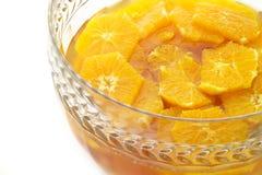 Rebanadas anaranjadas que adoban en un tazón de fuente cristalino imagen de archivo