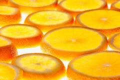 Rebanadas anaranjadas que brillan intensamente en un fondo blanco Modelo Imagen de archivo libre de regalías