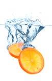 Rebanadas anaranjadas que caen en el agua Fotografía de archivo