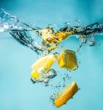Rebanadas anaranjadas que caen en el primer del agua, macro, agua del chapoteo, burbujas Imagen de archivo