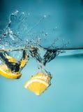 Rebanadas anaranjadas que caen en el primer del agua, macro, agua del chapoteo, burbujas Fotos de archivo libres de regalías