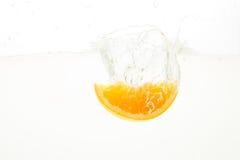 Rebanadas anaranjadas que caen profundamente debajo del agua con un chapoteo grande Fotos de archivo
