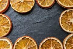 Rebanadas anaranjadas secadas brillantes en un fondo texturizado de piedra, espacio de la copia, endecha plana, visión superior fotos de archivo