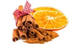 Rebanadas anaranjadas secadas con los palillos de canela y polvo del canela en blanco Fotos de archivo libres de regalías