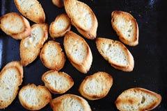 Rebanadas cocidas curruscantes del baguette en una bandeja de la hornada Foto de archivo libre de regalías