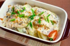 Rebanadas cocidas de la patata debajo del queso Foto de archivo