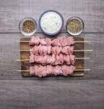Rebanadas crudas de pavo en los pinchos con cierre rústico de madera de la opinión superior de la salsa de ajo y del fondo de los Imagen de archivo