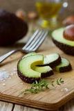 Rebanadas de aguacate con aceite de oliva, tomillo de la hierba y ajo fotografía de archivo libre de regalías