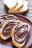 Rebanadas de baguette con crema del chocolate Imagenes de archivo