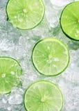 Rebanadas de cales verdes sobre los cubos de hielo machacados Fotos de archivo libres de regalías