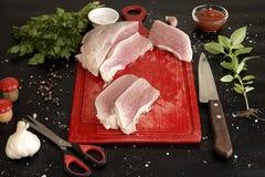 Rebanadas de cerdo crudo en la tajadera roja Foto de archivo
