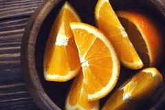 Rebanadas de cuenco de madera anaranjado en la tabla de madera Visión superior entonado Foto de archivo