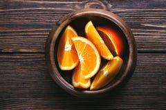 Rebanadas de cuenco de madera anaranjado en la tabla de madera Visión superior entonado Imágenes de archivo libres de regalías