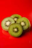 Rebanadas de fruta de kiwi aisladas en el fondo rojo, tiro vertical Foto de archivo