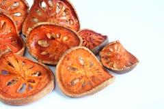 Rebanadas de fruta secada del bael en blanco imagenes de archivo