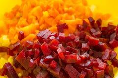 Rebanadas de golpe rojo hervido y de zanahorias en un tablero de madera foto de archivo libre de regalías