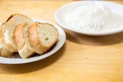 Rebanadas de harina del pan y de trigo en una placa blanca en la tabla Foto de archivo libre de regalías