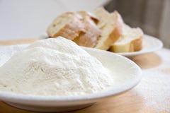 Rebanadas de harina del pan y de trigo en una placa blanca en la tabla Fotos de archivo libres de regalías