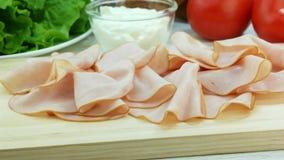 Rebanadas de jamón del cerdo en el tablero de madera, haciendo el bocadillo, ingredientes en fondo metrajes