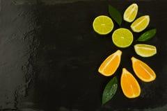 Rebanadas de la cal y del limón en fondo negro Fotografía de archivo