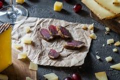 Rebanadas de la carne secada, manchego español tajado del queso duro en el corte de madera, toscano italiano cortado del pecorino Foto de archivo libre de regalías