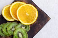 Rebanadas de la fruta cítrica y goma del kiwi en superficies de madera Kiwi y cortado imagenes de archivo