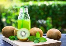 Rebanadas de la fruta de kiwi, jugo en una botella Imágenes de archivo libres de regalías