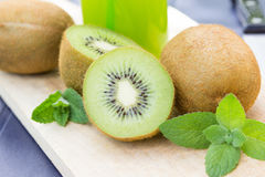 Rebanadas de la fruta de kiwi, jugo en una botella Fotos de archivo libres de regalías