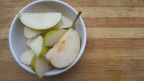 Rebanadas de la fruta de la pera en cuenco Foto de archivo libre de regalías