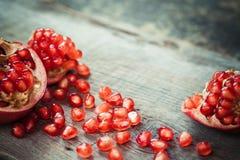 Rebanadas de la granada y semillas de la fruta del granate en la tabla fotos de archivo