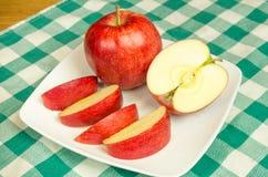 Rebanadas de la manzana de Jonagold en una placa blanca Foto de archivo libre de regalías