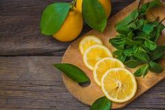 Rebanadas de la menta fresca y del limón en el tablero de madera Imagen de archivo