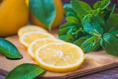 Rebanadas de la menta fresca y del limón en el tablero de madera Imagen de archivo libre de regalías