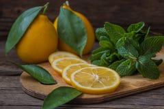 Rebanadas de la menta fresca y del limón en el tablero de madera Foto de archivo