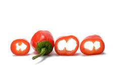 Rebanadas de la pimienta de chiles rojos aisladas en el fondo blanco Imagenes de archivo