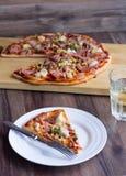 Rebanadas de la pizza en una placa, tabla blanca, cubiertos al vidrio de soda Imagen de archivo libre de regalías