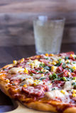 Rebanadas de la pizza en una placa, una tabla blanca y un vidrio de soda Foto de archivo