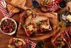 Rebanadas de la pizza que son servidas en las placas de madera Fotos de archivo libres de regalías