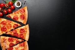 Rebanadas de la pizza de salchichones en fondo negro imagenes de archivo